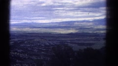 1967: a man is enjoying the panoramic view of vast land under the overcast sky Stock Footage