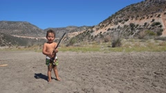 Boy with a stick on the lonely beach Stock Footage