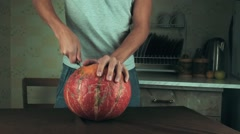 Young men carves jack o lantern out of pumpkin on a kitchen table using knife Stock Footage