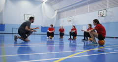 4k, A male coach talking to a group of teenage girls during a physical education Stock Footage