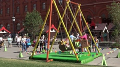Children swinging on a giant swing on Manezh Square in Moscow, Russia Stock Footage
