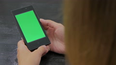 Woman looking at smartphone with green screen Stock Footage