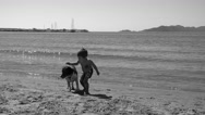 BW Boy plays with a dog at the seafront Stock Footage