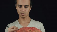 Young men in white t-shirt draws scary face on pumpkin with a marker Stock Footage