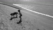 BW Kid plays with a dog at the lonely beach Stock Footage