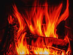Fireplace with wood and fire Stock Photos