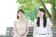 Attractive young girls sitting in a park Stock Photos
