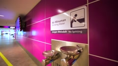 Drinking water in KL International airport. Man's man turns on and off the tap. Stock Footage