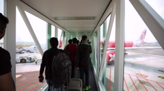 People board the plane in Kuala Lumpur International airport, Malaysia Stock Footage