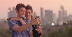 Attractive couple taking photographs in front of Los Angeles skyline 4K Stock Footage