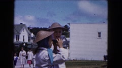 1961: two girls wearing woven oriental hats are taking turns looking through Stock Footage