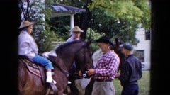 1961: two boys on horses ready for ride with jockeys standing beside MICHIGAN Stock Footage