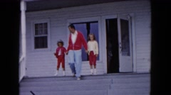1961: father and daughters hold hands and walk down front porch steps MICHIGAN Stock Footage