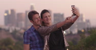 Attractive couple taking selfies in front of Los Angeles skyline at dusk 4K Stock Footage