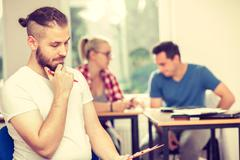 Student boy in front of her mates in classroom Stock Photos