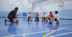 4k, A male coach talking to a group of teenage boys during a physical education  Stock Footage