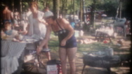 Family and friends picnic in the park next to lake, 3687 vintage home movie Stock Footage