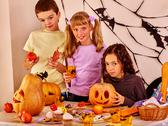 Children look forward to Halloween. They make carved pumpkin. Stock Photos