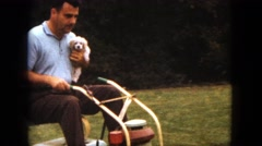 1963: man on a riding mower carrying a young cocker spaniel in his arm MAINE Stock Footage
