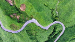 Aerial view of Aso mountain field and winding road Stock Footage