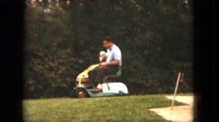 1963: man on riding mower outdoors with his little white poodle MAINE Stock Footage
