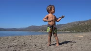 Small warrior with a stick on the lonely beach Stock Footage