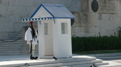 Guard in dress uniform beside a sentry box at the parliament in athens, greece Stock Footage