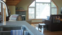 A dolly shot of a kitchen sink and living room Stock Footage