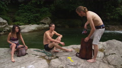 Group of friends drinking beer at camp site Stock Footage