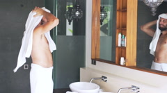 Young man after bath drying hair and face with towel in bathroom Stock Footage