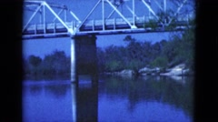 1950: view of a massive steel bridge over a wide river surrounded by trees  Stock Footage