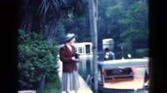 1950: a lady is strolling along a sidewalk bordering a lake with palm trees  Stock Footage