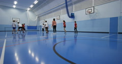 4K Sports teacher coaching male & female pupils during school basketball game Stock Footage