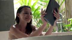 Young, happy woman using tablet during bath in open bathroom  Stock Footage