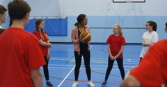 4K Sports teacher with pupils on school basketball court, explaining how to play Stock Footage