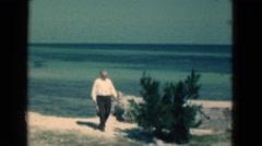 1950: a man fully dressed walking along the ocean coastline FLORIDA Stock Footage