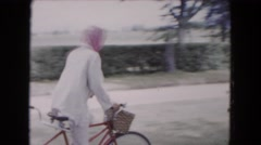 1961: a woman with scarf riding a bike behind several horse-drawn carriages Stock Footage
