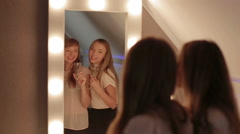 Two Girls Primp In A Mirror Together smiling dance Stock Footage