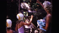 1961: a blonde haired mother and her two daughters feed a caged monkey MINNESOTA Stock Footage