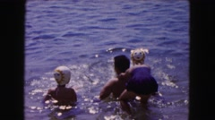 1961: kid playing in shallow water with adults and another child MINNESOTA Stock Footage