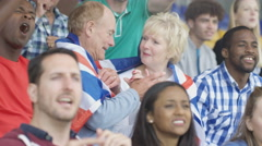 4K Affectionate mature couple in crowd at sports event draped in British flag Stock Footage