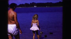 1961: father with two girls watch carefully as they wade in shallow water Stock Footage