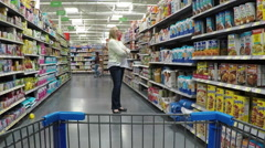 Grocery store pan across food shelf to house wife POV HD Stock Footage