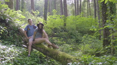 Hikers Rest On A Fallen Tree And Chat/Flirt Stock Footage