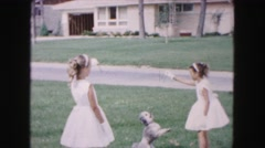 1961: two girls in white dresses and gloves playing with dog in yard MINNESOTA Stock Footage