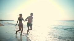 Happy couple in swimwear running along the seashore slow motion Stock Footage