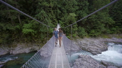 Adventurous Hiking Couple Cross A Suspension Bridge Above A River Stock Footage