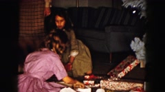 1961: mom and two daughters opening presents on christmas morning MINNESOTA Stock Footage