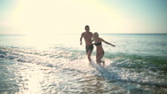 Young beautiful couple smiling going out of ocean. Slow motion. Stock Footage