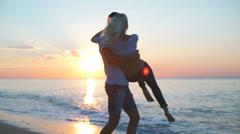 Young beautiful couple smiling whirling at seashore at sunrise. Slow motion. Stock Footage
